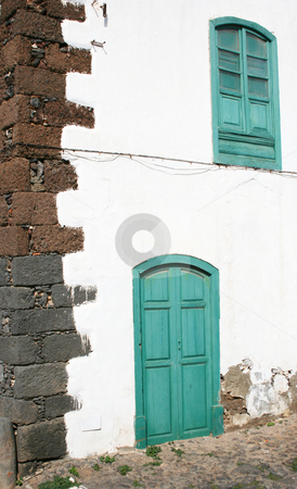 Green Door and Window stock photo, Old fashioned but traditional style of window and door in Teguise, Lanzarote. by Helen Shorey
