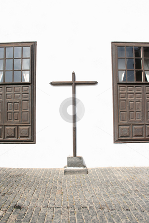 Cross Between two Windows stock photo, A very simple and plain wooden cross attached to the outside wall of a monastery in the town of Teguise, Lanzarote by Helen Shorey