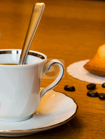 Coffee time stock photo, Closeup of a ceramic coffee cup with coffee beans and a cake in background. by FEL Yannick