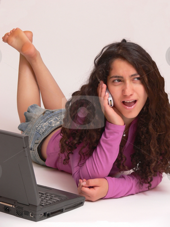 Young girl on the phone    stock photo, A young girl laying on the floor with her nice long curly dark hair working on the laptop and got a surprising phone call. On white background. by Horst Petzold