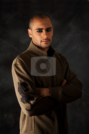 Dramatic Hispanic guy stock photo, Handsome African Hispanic guy frowning with strong macho expression and dark eyes in green vest with black tiger on sleeve by Paul Hakimata