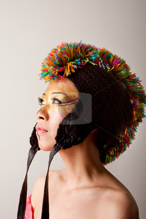 Colorful mohawk hat stock photo, Beautiful Asian female face with a colorful mohawk hat with straps, gold and purple makeup, isolated by Paul Hakimata