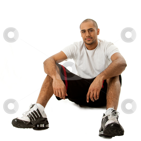 Sporty guy sitting stock photo, Sporty handsome African Hispanic guy sitting on floor, isolated by Paul Hakimata
