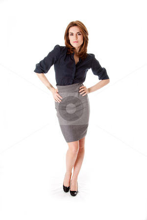 Beautiful business woman stock photo, Beautiful brunette business woman with sexy attitude standing wearing gray skirt and blue blouse with hands on hips, isolated by Paul Hakimata