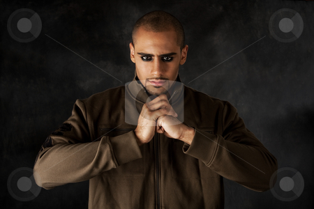 Dramatic Hispanic guy stock photo, Handsome African Hispanic guy frowning with strong mad macho expression and dark eyes in green vest and hands in a fist by Paul Hakimata