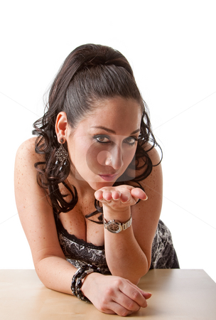 Sexy woman blowing kisses stock photo, Beautiful sexy caucasian woman blowing kisses while leaning with elbows on table, isolated by Paul Hakimata
