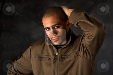 Dramatic Hispanic guy stock photo, Handsome African Hispanic guy frowning with strong macho expression and dark eyes in green vest and hand on head by Paul Hakimata