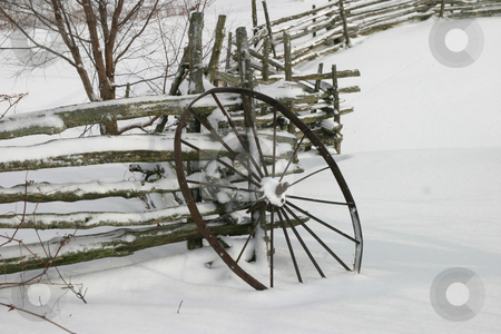 Winter Wheel stock photo, An old iron wagon wheel propped up against a split rail fence, winter scene with lots of snow. by Rick Parsons