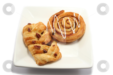 Overhead view of Danish pastries stock photo, Iced cinnamon swirl and a maple and pecan danish pastry on a square white plate by Helen Shorey
