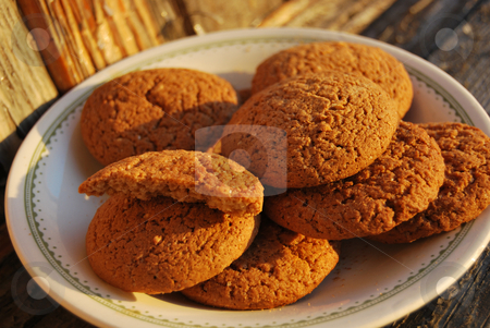 Plate with oatmeal cakes in the sunset stock photo,  by Leyla Akhundova