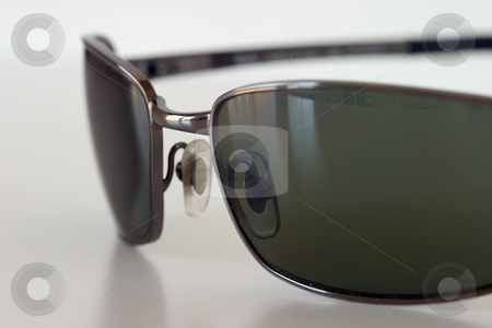 Sunglasses on a white surface stock photo, Macro view of sunglasses sitting on a white surface. by Rick Parsons