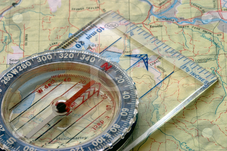 Compass and Map stock photo, Close-up view of a compass sitting on a topo map. by Rick Parsons