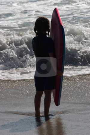 Little Surfer Girl stock photo, A young girl contemplates the ocean in front of her, as she clutches her boogie board.  She is silhouetted by the late afternoon sun. by Rick Parsons