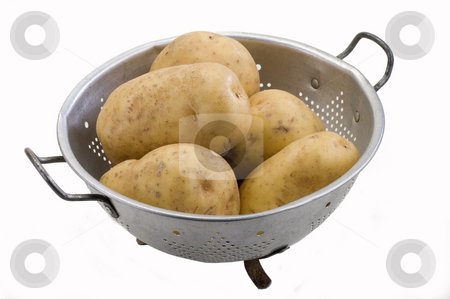 Potatoes stock photo, Potatoes in a metal colander on white by Jonathan Hull