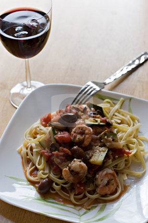 Shrimp With Fettuccini Dish stock photo, A delicious shrimp and pasta dish along with a glass of red wine. by Todd Arena