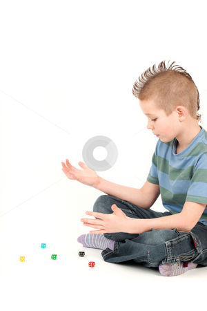 Portrait of young boy with mohawk playing with dice, studio shot stock photo, Portrait of young boy with mohawk playing with dice, studio shot by Tom P.