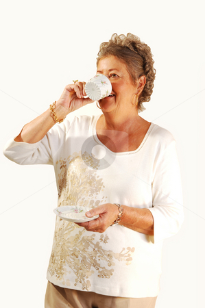 Senior woman tingling coffee. stock photo, Elderly retired woman standing at home and enjoying a cup of coffee, on white background. by Horst Petzold