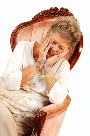 Worried senior woman. stock photo, Senior woman sitting in an pink armchair with her head in her hands worrying over the future, on white background. by Horst Petzold