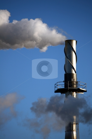 Tall Smokestack, Air Pollution stock photo, A tall smokestack at a factory, billowing smoke into the air on a blue sky day by Tom and Beth Pulsipher