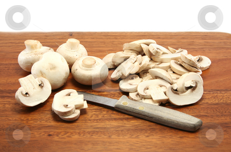 Mushroom Preparation stock photo, Sliced and whole white button mushrooms on a wooden chopping board with a paring knife by Helen Shorey