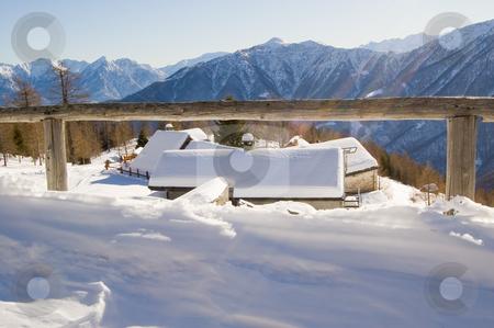 Sunny winter mountain landscape stock photo, Sunny winter mountain landscape framed by a wooden fence; Alps, Italy by Roberto Marinello