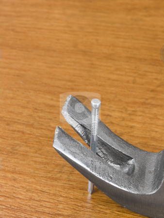 Hammer Pulling nail stock photo, Hammer pulling nail on a wooden background by John Teeter