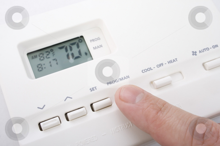 Climate control stock photo, Closeup shot of male hand adjusting thermostat to 70 degrees by iodrakon