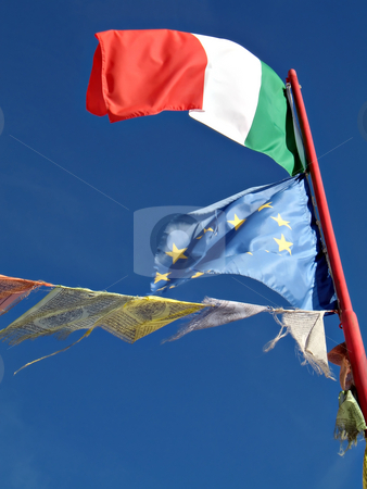 High mountain flags stock photo, Italian flag, european union flag and prayer flag wave in the peace of high mountain refuge by Roberto Marinello