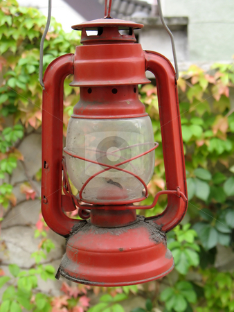red oil lamp stock photo, An old oil lamp on a coming red woodbine by Roberto Marinello