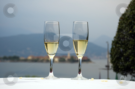 Romantic dinner on the lake shore stock photo, Two glasses of white wine in a restaurant on the lake Maggiore shore, Italy by Roberto Marinello