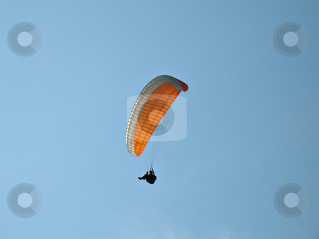Orange Paraglide  stock photo, A paraglider il flying in the blue sky with his colourful paraglide by Roberto Marinello