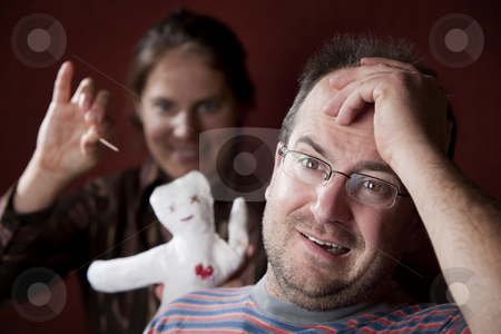 Upset woman with vioodoo doll and guilty man stock photo, Guilty man with upset woman poking voodoo doll in the background by Scott Griessel