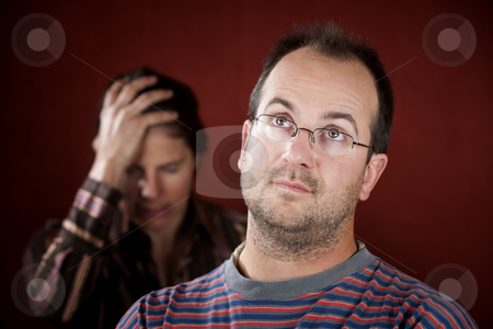 Upset woman and guilty man stock photo, Guilty man with upset woman in the background by Scott Griessel