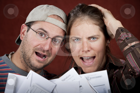 Couple with too many bills stock photo, Young couple upset over too many bills by Scott Griessel