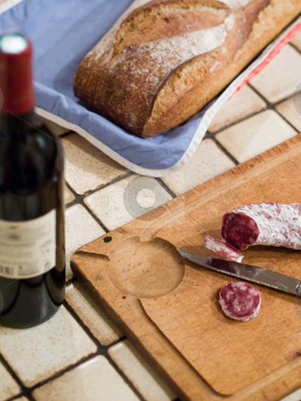 Country french snack stock photo, French dry sausage on a wooden cutting board with slices cut off and a knife. A bread and a bottle of wine is present. by FEL Yannick