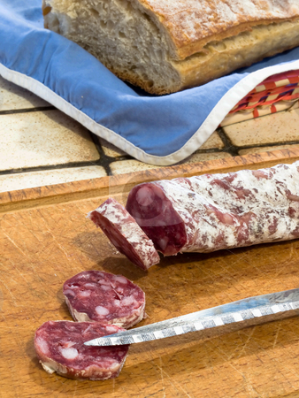 Country french snack stock photo, French dry sausage on a wooden cutting board with slices cut off and a knife. A bread is present in  background. by FEL Yannick