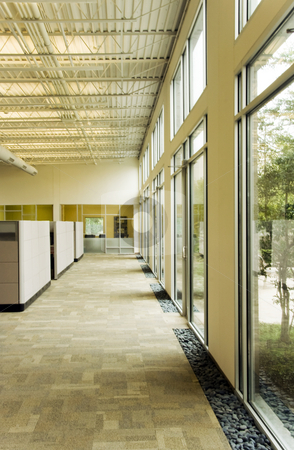 Office Work Space stock photo, A office building hallway next to some large glass windows by Kevin Tietz