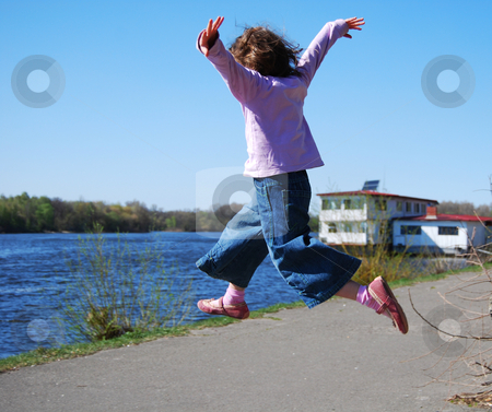 Flying child stock photo, Jumping girl in blue jeans, pink shoes and lilac pullover against water background by Leyla Akhundova