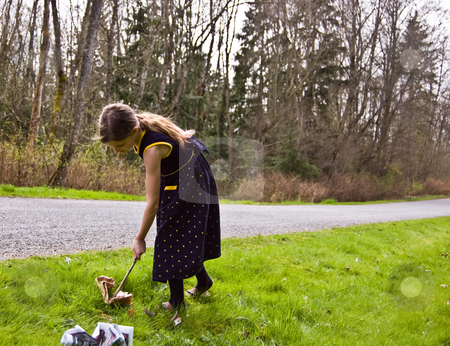Young Girl Picking up Litter with a Stick stock photo, 8 year old Caucasian child is picking up litter on the side of the road with a stick.  She's trying to practice good ecology at a young age.  She has long hair and is wearing a navy blue flowered dress. by Valerie Garner