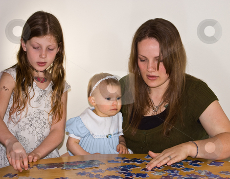 Young Mom and 2 Girls Doing Jigsaw Puzzle Together stock photo, A young mom in her 20's is helping a 8 year old girl and baby to do a jigsaw puzzle.  Candid, real life facial expressions make this a precious photo. by Valerie Garner