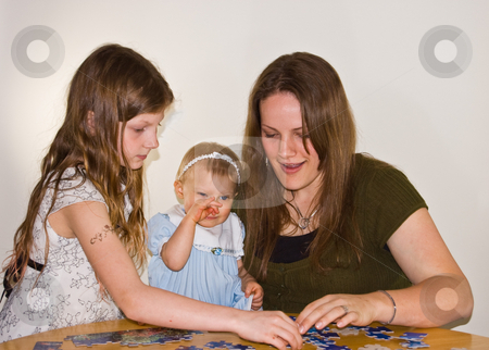 Mom and Girls Doing Puzzle stock photo, This brunette young mom is doing a puzzle with 2 young girls.  The baby is rubbing her nose as she's getting sleepy.  Family bonding time while learning too. by Valerie Garner