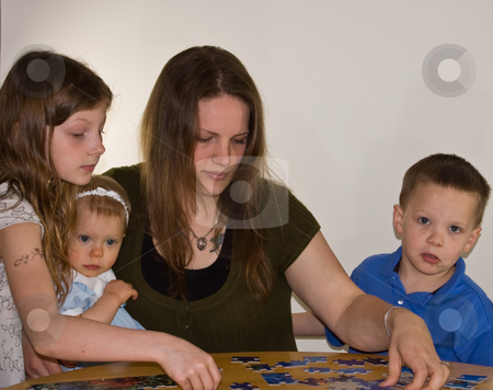 Young Mother and 3 Children Working On Puzzle stock photo, Young mother is working on a puzzle at the table with 3 children, 2 girls and 1 boy for this family bonding time. by Valerie Garner