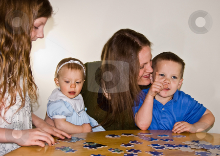Mom and Three Kids Doing A Puzzle stock photo, Mom and 3 kids, 4 year boy, 8 year old girl, and baby girl are enjoying family time together by doing a puzzle on a table. by Valerie Garner