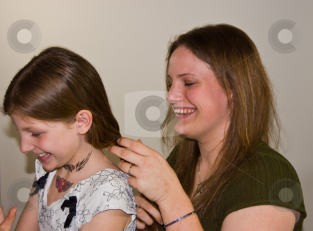 Mother Braiding Daughter's Hair stock photo, This young attractive Caucasian mom is braiding her 8 year old daughter's long hair.  Both are enjoying and having fun with this normal day to day activity. by Valerie Garner