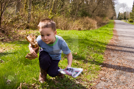 Young Boy Picking Up Garbage - Ecology stock photo, A young 4 year old Caucasian boy is picking up garbage on the side of the road to do his share for helping ecology and environmental issues. by Valerie Garner