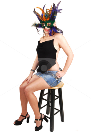 Beautiful woman with feather mask. stock photo, An lovely white young woman in an short jeans skirt and black top sitting on the green bar chair and a feather mask over her face. by Horst Petzold