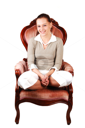 Young pretty woman. stock photo, An lovely smiling young woman with her legs under her butt sitting in the studio in an armchair and looking at the camera. by Horst Petzold