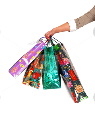 The arm of a woman with shoping bags.  stock photo, A woman's arm holding several colorful shopping bags in the picture with white background. by Horst Petzold