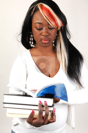 Young woman with books. stock photo, A young Jamaican girl with nice colored hair smiling and holding some books in her hands. by Horst Petzold