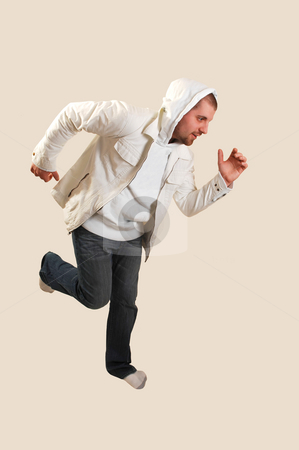 Young man running. stock photo, A young athletic man posing running in the studio with an white jacket and the hood over his head, on beige background. by Horst Petzold